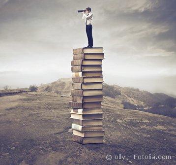 Foto Mann mit Fernglas auf Büchern